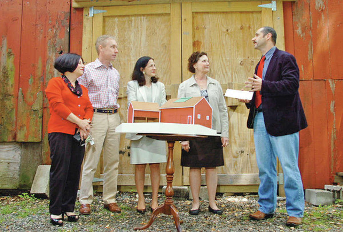 Photos by Erik Trautmann Above, Todd Levine, director of Historic Barns, Connnecticut Trust for Historic Preservation, right, presents a check for $5,000 to Rev. Suzanne Wagner of the Wilton Congregational Church, second from right, while State Rep. Gail Lavielle, R-143, center, William Follett, trustee of the Wilton Congregational Church, and State Sen. Toni Boucher, R-26, look on Wednesday morning. The grant will be used to help continue to restore the Comstock Barns, which were built in the 1850s. At left, a model of the restored barn sits near the exterior of the historic structure.