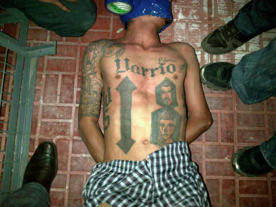 "In this undated image obtained by the Associated Press on Feb. 14, 2013, a man lies on the ground surrounded by unidentified people. On Jan. 9, 2013, neighbors of Kevin Said Carranza Padilla, 28, known in the gang world as ""Teiker,"" saw police come and take him and his girlfriend without a shot. The next morning, Jan. 10, Honduras' major newspaper, El Heraldo, reported that police had captured Carranza in connection with the murder of a police commander months earlier, publishing this photo of a shirtless, tattooed young man lying on the ground, his hands behind his back, his face partially wrapped in blue duct tape, the roll still attached. Carranza's mother, Blanca Alvarado, recognized him from his tattoos. (AP Photo) / AP"