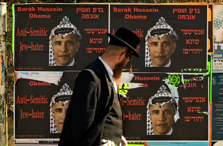 FILE -- In this Sunday, June 14, 2009 file photo, an Ultra Orthodox Jewish man walks past posters depicting US President Barack Obama wearing a traditional Arab headdress, in Jerusalem, Sunday, June 14, 2009. President Barack Obama's vow to take his message straight to the public during his first presidential visit to Israel next week will be a tough sell with many Israelis who consider him naive, too soft on the nation's enemies and even hostile to Prime Minister Benjamin Netanyahu. (AP Photo/Sebastian Scheiner, File) / AP
