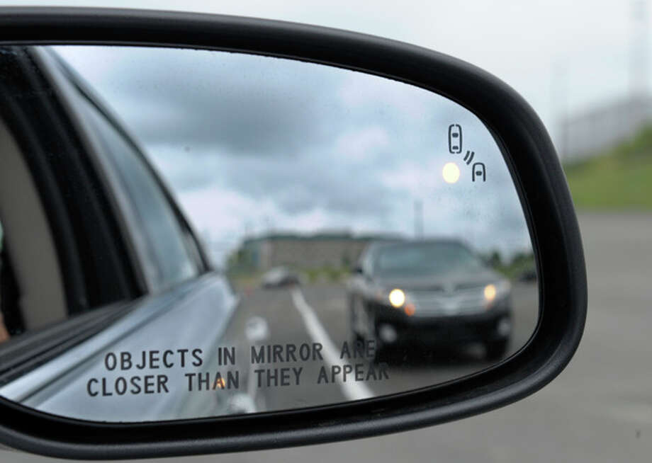 In this photo taken Tuesday, May 22, 2012, professional test driver J.D. Ellis of Cincinnati, Ohio, demonstrates the side mirror warning signal in a Ford Taurus at an automobile testing area in Oxon Hill, Md. The display at a recent transportation conference was a peek into the future of automotive safety: cars that to talk to each other and warn drivers of impending collisions. Later this summer, the government is launching a yearlong, real-world test involving nearly 3,000 cars, trucks and buses using volunteer drivers in Ann Arbor, Mich. (AP Photo/Susan Walsh) / AP