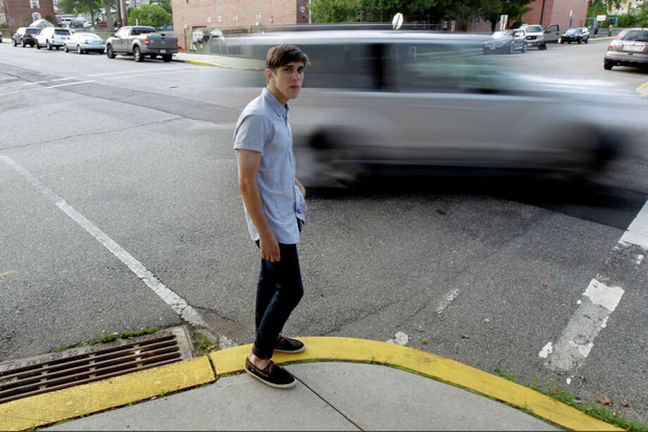 Dylan Young, 18, poses for The Associated Press as a vehicle cruises by, Wednesday, June 6, 2012, in North Arlington, N.J. Young, a senior at North Arlington High, was in a fender-bender accident caused by being distracted while texting and driving. More than half of high school seniors say they text or email while driving, according to a jarring new study that offers the first federal statistics on how common the dangerous habit is in teens. The Centers for Disease Control and Prevention released the numbers Thursday, June 7, 2012. They come from a 2011 survey of about 15,000 high school students across the country. The study found 58 percent of high school seniors said that, in the previous month, they had texted or emailed while driving. (AP Photo/Julio Cortez) / AP