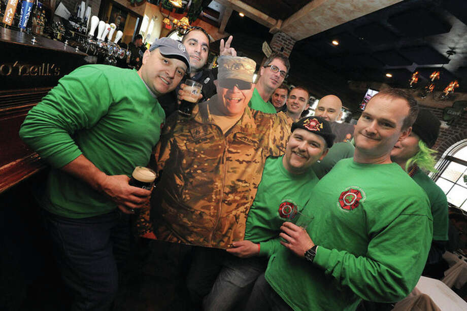 Westport firefighter and Army Staff Seargent Pete Nichio's favorite holiday is St. Patrick's Day. Since he can't be with fellow Westport firefighters because he is serving in Afghanistan they brought a cardboard cutout of him to O'Neills Sunday. hour photo/Matthew Vinci