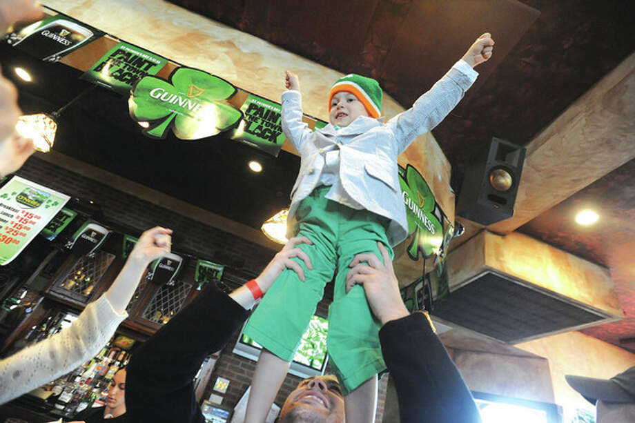 Hour photo/Matthew Vinci3 year old Logan Prescott gets a lift from his dad Sunday during the St. Patrick's Day festivities at O'Neills in Norwalk.