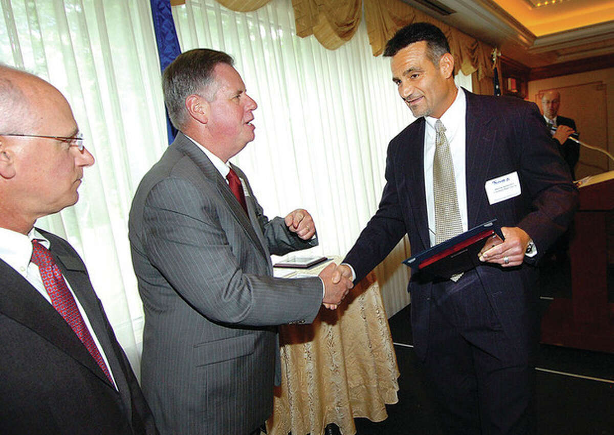 Hour photo/ Alex von Kleydorff Greater Norwalk Chamber of Commerce President Edward Musante Jr. shakes hands with Frank DiNicola as he and his brother Dominick are awarded a 2012 Small Business Award for Continental Manor.