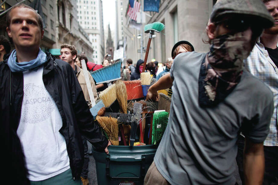 Protestors participating in the Occupy Wall Street protest pull a garbage can of brooms during a march towards Wall Street on Friday, Oct. 14, 2011, in New York. At least ten people were arrested during the march, which began after protestors heard the news that the owners of Zuccotti Park had withdrawn their request to have the park cleaned by the New York Police Department. (AP Photo/Andrew Burton) / FRE170478 AP