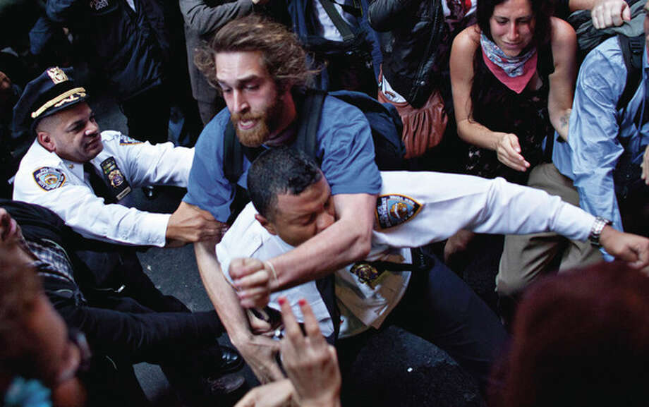 A man affiliated with the Occupy Wall Street protests tackles a police officer during a march towards Wall Street in New York, on Friday, Oct. 14, 2011. The official cleanup of a plaza in lower Manhattan where protesters have been camped out for a month was postponed early Friday, sending up cheers from a crowd that had scrambled to scrub the park on its own out of fear the effort was merely a pretext to evict them. (AP Photo/Andrew Burton) / FRE170478 AP