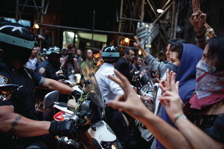 Protestors participating in the Occupy Wall Street protests face police during a march towards Wall Street Friday, Oct. 14, 2011, in New York. At least ten people were arrested during the march, which began after protestors heard the news that the owners of Zuccotti Park had withdrawn their request to have the park cleaned by the New York Police Department. (AP Photo/Andrew Burton) / FRE170478 AP