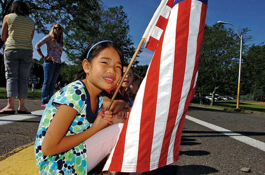 Miller-Driscoll first grader Sydeny Lillis waits for the Wilton police to carry the Special Olympics Torch by as they run through town. Hour photo / Erik Trautmann / (C)2012, The Hour Newspapers, all rights reserved
