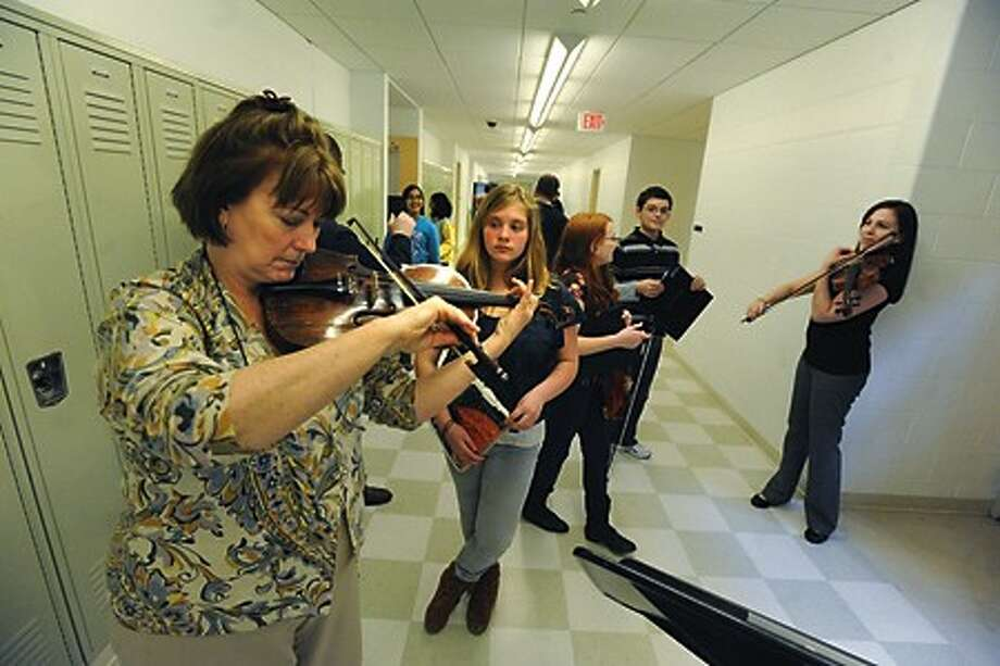 Barbara DiFranco tunes a viola for West Rocks student Emma Cooney Tuesday afternoon at Brien McMahon High School at rehearsals for the all-city strings concert. hour photo/matthew vinci