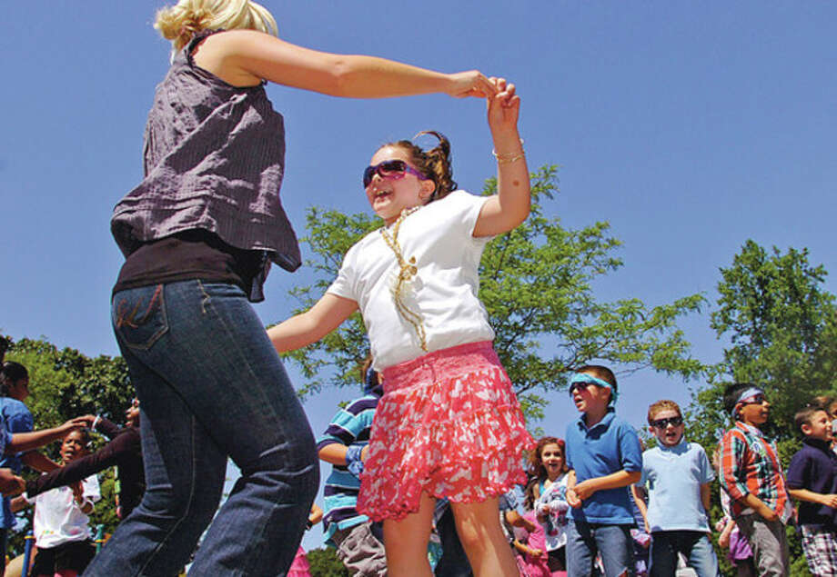 Second Grader Elizabeth Sccott grabs first grade teacher Lisa Longo during the second graders rendition of We Got the Beat as Wolfpit Elementary School holds it end of year celebration, Wolfpit Day Friday.Hour photo / Erik Trautmann / (C)2012, The Hour Newspapers, all rights reserved
