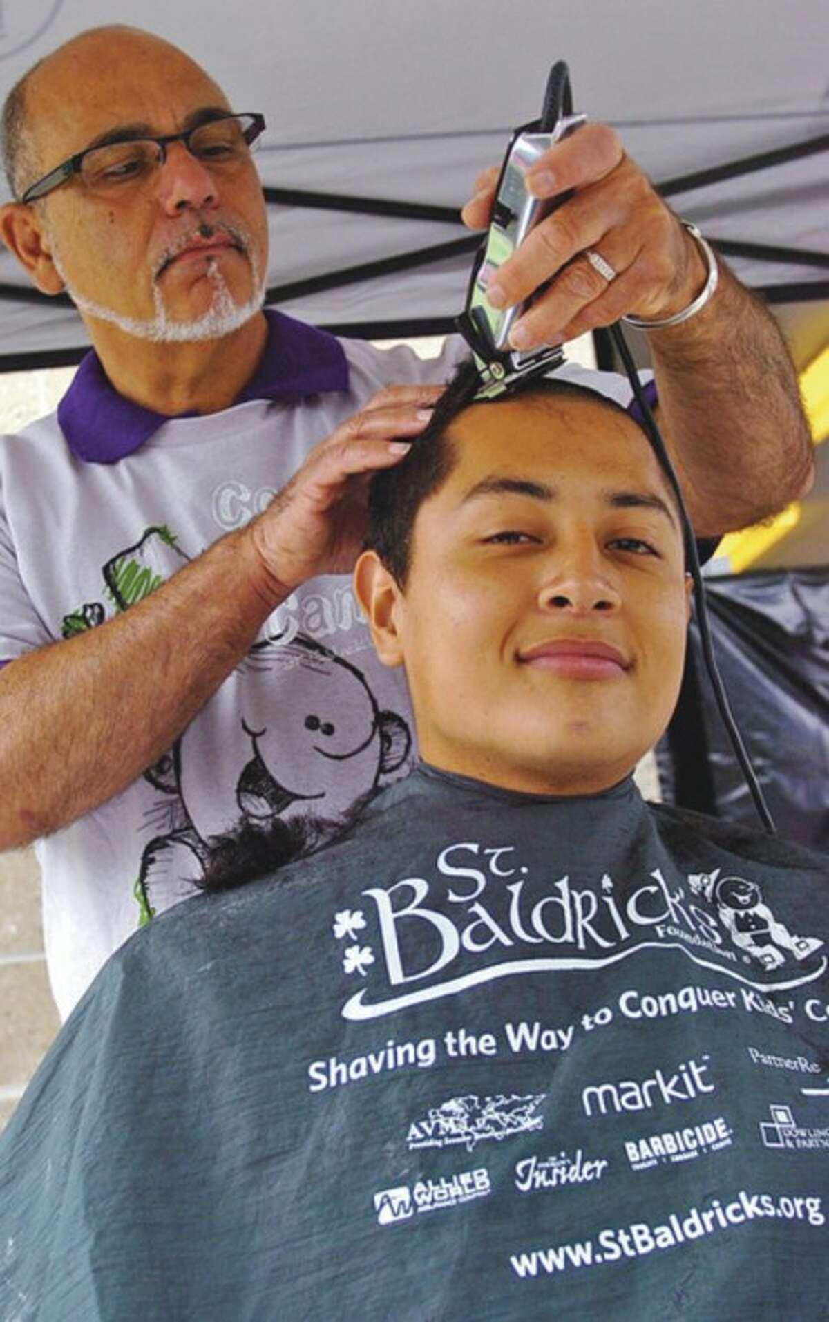 Norwalk High School senior Erick Rivera gets his head shaved Saturday.