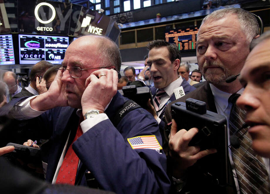 In an April 12, 2012 file photo traders Frederick Reimer, left, Gregory Rowe, center, and Robert Moran, second from right, work on the floor of the New York Stock Exchange. U.S. futures augured a lower open on Wall Street Friday June 8, 2012. Dow Jones industrial futures fell 0.7 percent to 12,316 and S&P 500 futures lost 0.8 percent at 1,299.60. (AP Photo/Richard Drew) / AP2012