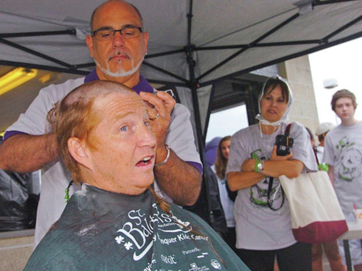 Norwalk High School guidance counselor Dan Sullivan gets his head shaved Saturday.