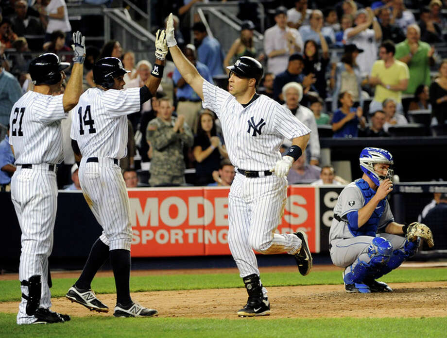 New York Yankees' Mark Teixeira, second from right, runs past New York Mets catcher Josh Thole, right, to high-five teammates Raul Ibanez (27) and Curtis Granderson (14) after hitting a two-run home run off Mets starting pitcher Dillon Gee in the sixth inning of an interleague baseball game on Saturday, June 9, 2012, at Yankee Stadium in New York. Granderson also scored on the home run. (AP Photo/Kathy Kmonicek) / FR170189 AP