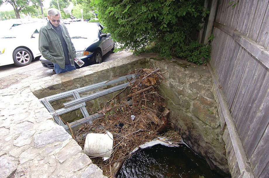 Hour photo / Alex von KleydorffArt Jackson looks into the clogged storm drain near his house on New Canaan Avenue recently. / 2012 The Hour Newspapers