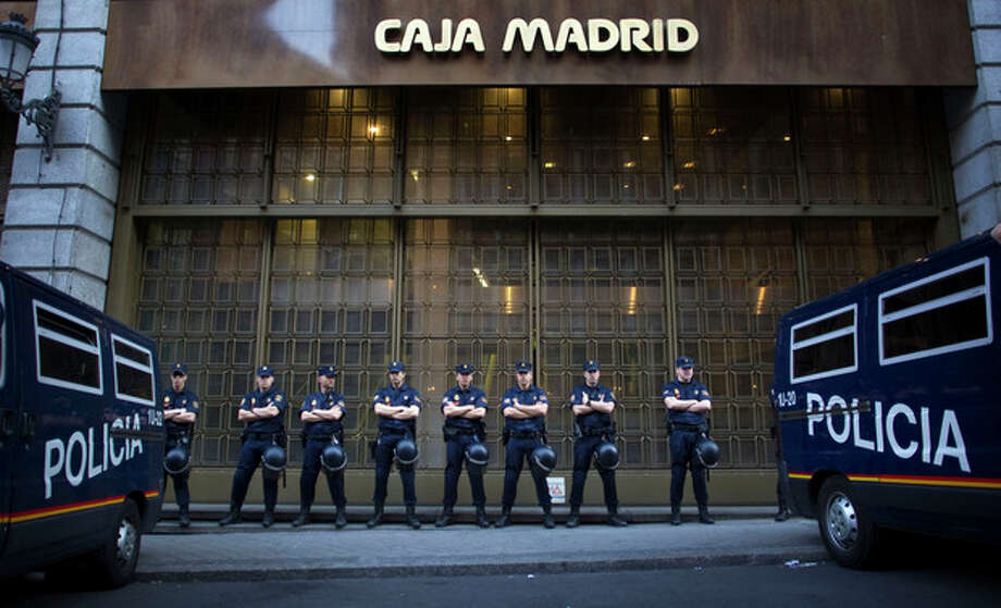 File - In this May 14, 2012 file photo, riot police stand guard in front of a branch of the recently nationalized Caja de Madrid/Bankia bank during a protest in Madrid. Spain could ask for a European rescue of its troubled banks this Saturday June 9, 2012 when European finance ministers hold an emergency conference call to discuss the nation's hurting lending sector, a move that would turn the nation into the fourth from the 17-nation eurozone to seek outside help since the continent's financial crisis erupted two years ago. (AP Photo/Alberto Di Lolli, File) / AP