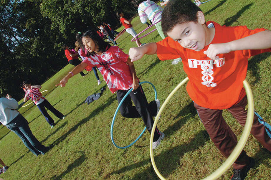 Jimmy Rosario and Arya Bhogte hula hoop at the Toquam Elementary School Jog-A-Thon Wednesday. / (C)2011, The Hour Newspapers, all rights reserved