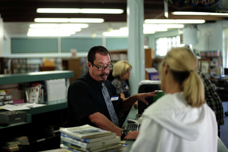 Library Branch Manager Matt Beatty, center, helps a customer at a San Diego Public Library Friday, June 8, 2012, in San Diego. Beatty has worked for the city as a librarian for more than 11 years. Voters in San Diego and San Jose overwhelmingly approved ballot measures last week to roll back municipal retirement benefits - and not just for future hires but for current employees. (AP Photo/Gregory Bull) / AP
