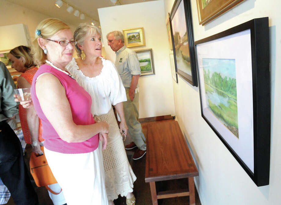 "Hour photo / Matthew VinciMary Verel and Kathy Siever looking at a pastel called ""Yost Street Marsh"" by local artist Jessica Huse at the Rowayton Arts Center on Sunday."