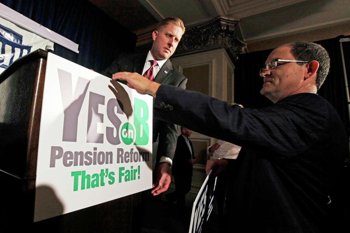 FILE - Supporters of Proposition B, which would roll back public pensions, adjust a sign before a rally on election day in San Diego in this Tuesday, June 5, 2012 file photo. For years, companies have been chipping away at workers' pensions. Now, two California cities may help pave the way for governments to follow suit. Voters in San Diego and San Jose, the nation's eighth- and 10th-largest cities, overwhelmingly approved ballot measures last week to roll back municipal retirement benefits -- and not just for future hires but for current employees. (AP Photo/Gregory Bull, File)