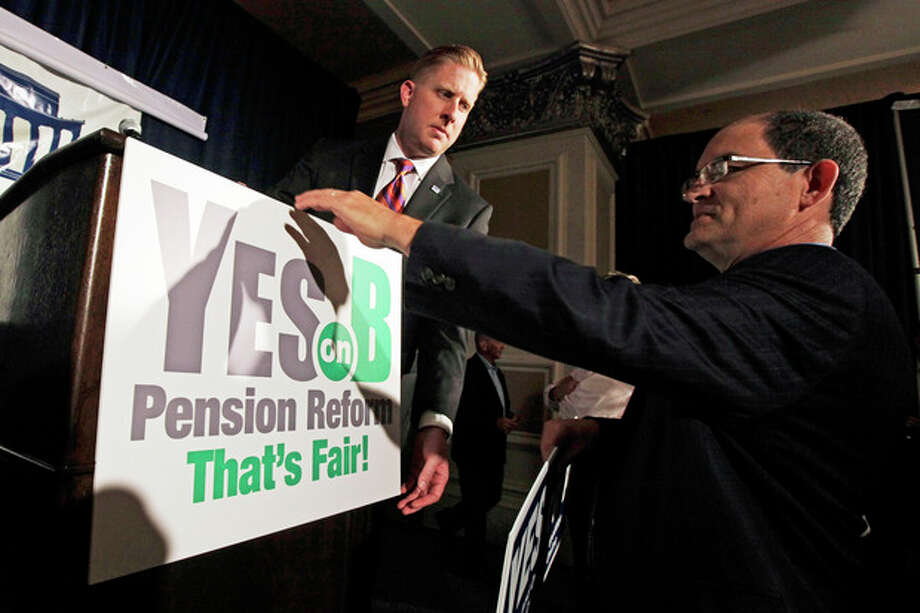 FILE - Supporters of Proposition B, which would roll back public pensions, adjust a sign before a rally on election day in San Diego in this Tuesday, June 5, 2012 file photo. For years, companies have been chipping away at workers' pensions. Now, two California cities may help pave the way for governments to follow suit. Voters in San Diego and San Jose, the nation's eighth- and 10th-largest cities, overwhelmingly approved ballot measures last week to roll back municipal retirement benefits -- and not just for future hires but for current employees. (AP Photo/Gregory Bull, File) / AP2012