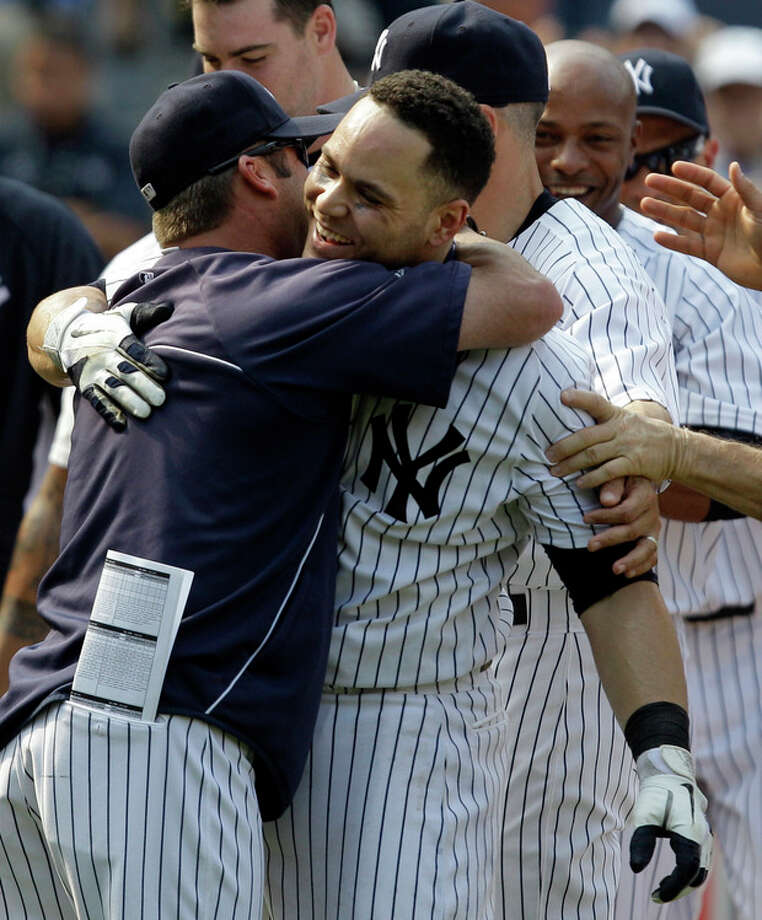 New York Yankees batting coach Kevin Long, left, embraces Yankees' Russell Martin after Martin's ninth-inning walk-off solo home run lifted them to a 5-4 victory over the New York Mets in a baseball game at Yankee Stadium in New York, Sunday, June 10, 2012. (AP Photo/Kathy Willens) / AP