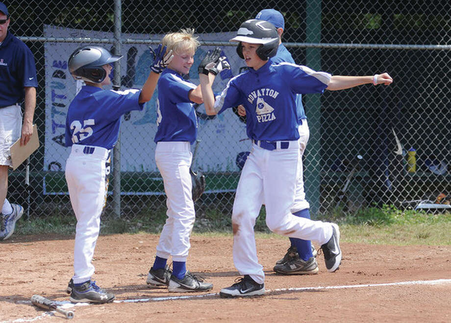 Rowayton Pizza's Bennett Close is greeted by teammates after home run vs. Sports Authority Sunday at the Rowayton little league Massey Cup championship. hour photo/Matthew Vinci