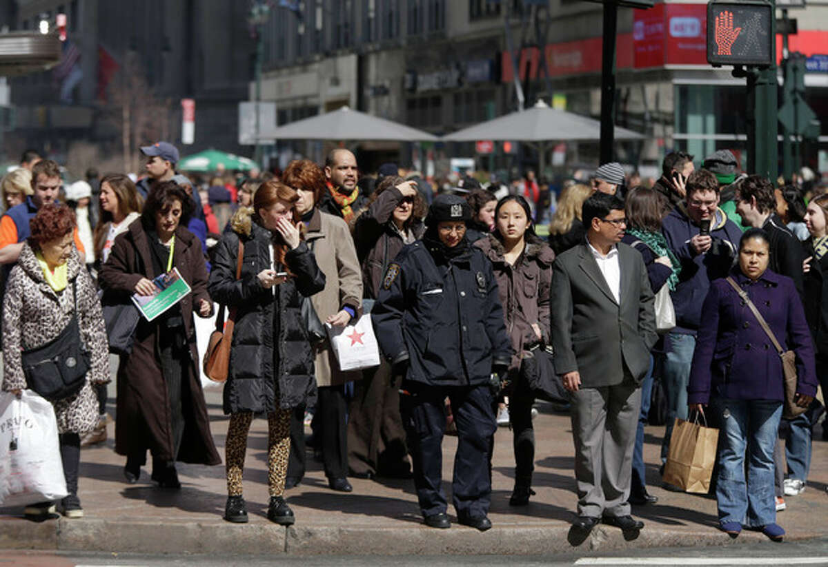 In this photo taken March 13, 2013, pedestrians wait to cross a New York street. An historic decline in the number of U.S. whites and the fast growth of Latinos are blurring traditional black-white color lines in the U.S. The demographic shift is now a potent backdrop to an immigration overhaul bill, being debated in Congress, that could offer a path to citizenship for 11 million mostly Hispanic illegal immigrants. (AP Photo/Seth Wenig)