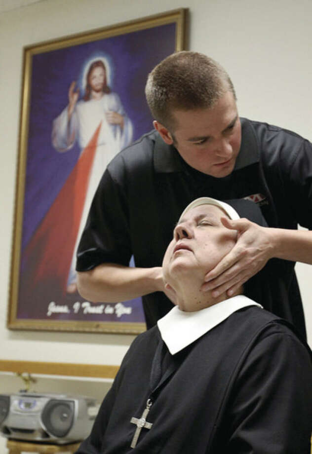 ADVANCE FOR SUNDAY MARCH 17 - In this Thursday March 7, 2013 photo, Sister Monica Mary, a nun with the Sisters of Charity of Our Lady Mother of the Church receives a chiropractic adjustment from Dr. Jason Sousa of Pro Health Chiropractic at the Motherhouse in Baltic, Conn. Sister Monica Mary had been suffering from a neuromuscular disorder and no treatment was helping until she experienced an adjustment from a chiropractor while in the hospital. Sister Monica Mary now receives adjustments twice a week. (AP Photo/Journal Inquirer, Jared Ramsdell) MANDATORY CREDIT