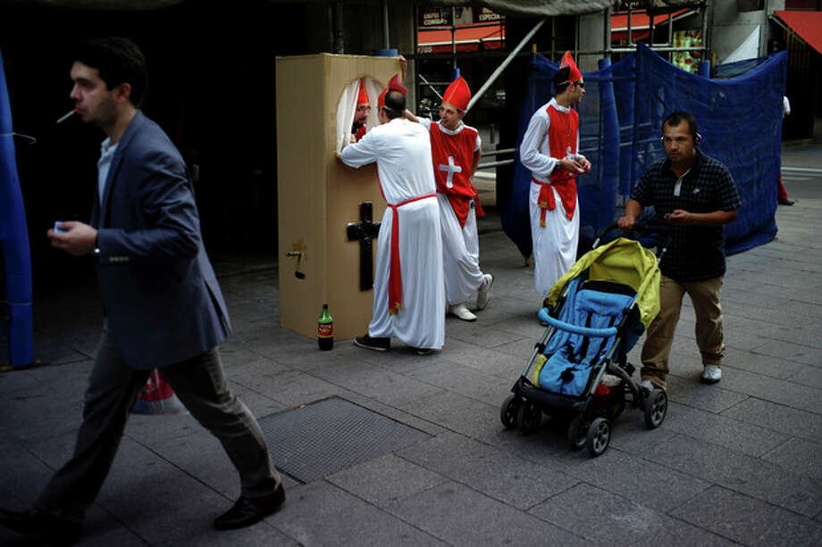 Spaniards dressed up like Bishops for a stag party play the role of a confessor in downtown Madrid, Saturday June 9 2012. Spain will ask for a bank bailout from the eurozone, becoming the fourth and largest country to seek help since the single currency bloc's debt crisis erupted.(AP Photo/Daniel Ochoa de Olza) / D.O.