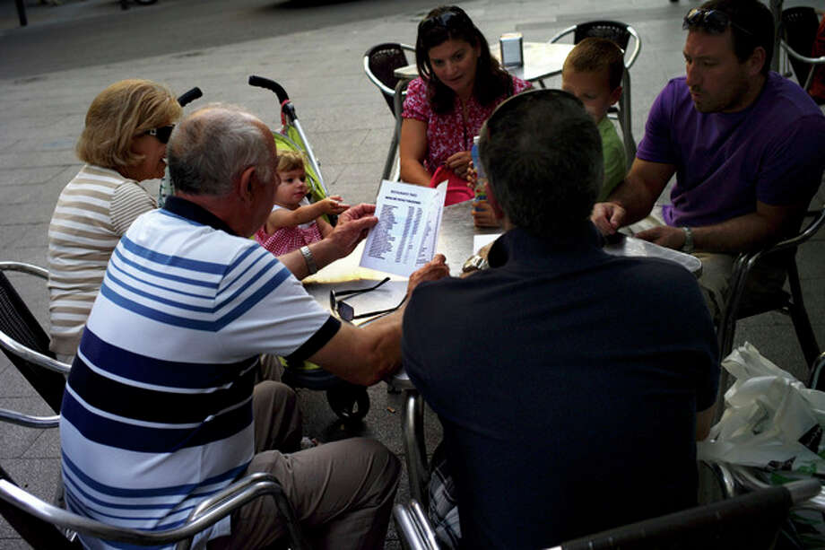 A Spanish family check the prices of tapas on a terrace in downtown Madrid, Saturday June 9, 2012. Spain will ask for a bank bailout from the eurozone, becoming the fourth and largest country to seek help since the single currency bloc's debt crisis erupted.(AP Photo/Daniel Ochoa de Olza) / D.O.