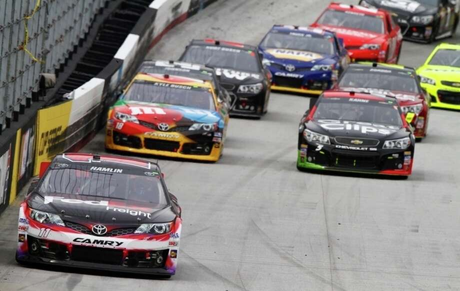 Denny Hamlin (11) leads driver Kyle Busch (18), driver Kasey Kahne (5) and others during the NASCAR Sprint Cup Series Food City 500 auto race on Sunday, March 17, 2013, in Bristol, Tenn. (AP Photo/Wade Payne) / FR23601 AP