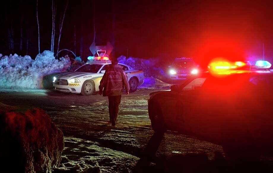 Police vehicles block a road just outside the town of Chertsey, Quebec, Sunday, March 17, 2013, during a search for escaped prisoners. A dramatic daylight jailbreak involving two Quebec inmates climbing a rope into a hovering helicopter swiftly escalated into a large police operation Sunday night in which at least one escapee was tracked down hours after he fled. (AP Photo/The Canadian Press, Graham Hughes) / The Canadian Press