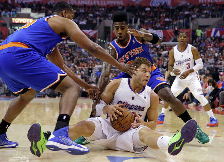 Los Angeles Clippers forward Blake Griffin (32) comes up with the ball in a floor scrum with New York Knicks forward Kurt Thomas, left, and forward Iman Shumpert (21) in the first half of an NBA basketball game in Los Angeles Sunday, March 17, 2013. (AP Photo/Reed Saxon) / AP
