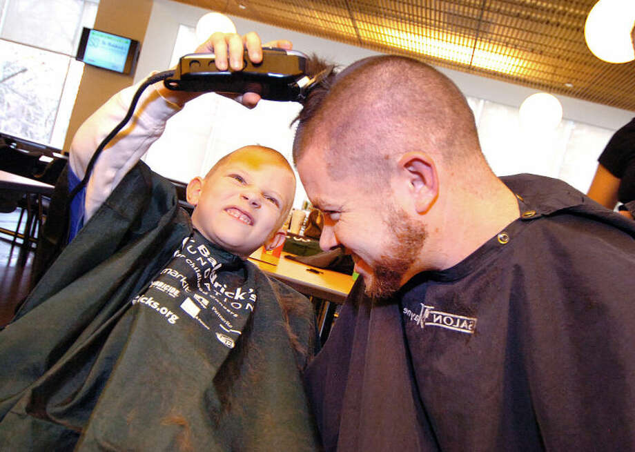 Hour Photo/Alex von Kleydorff. 6yr old Stephen Johnson gets the last of his father Dan's hair with the clippers at Gen Re St. Baldricks in Stamford