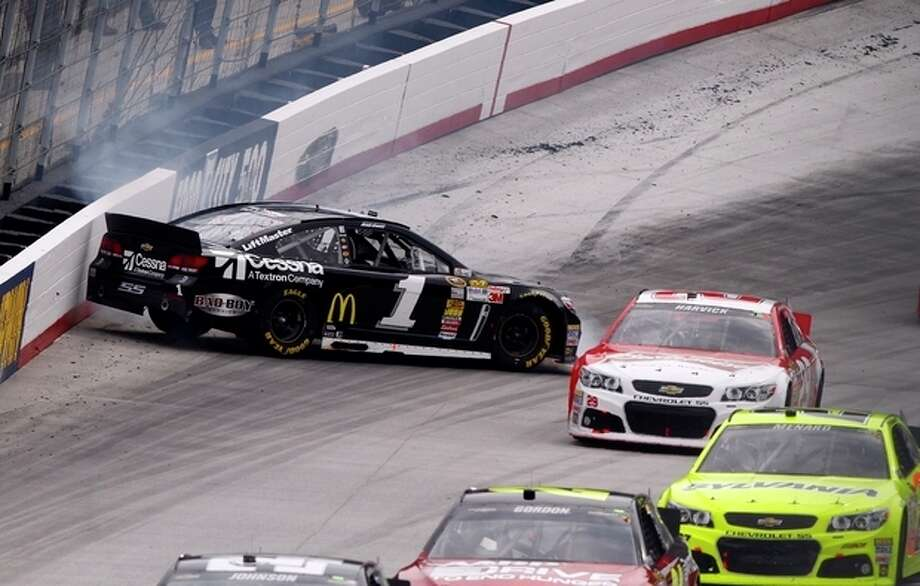 Jamie McMurray (1) spins as driver Kevin Harvick (29) and others get past during the NASCAR Sprint Cup Series Food City 500 auto race on Sunday, March 17, 2013, in Bristol, Tenn. (AP Photo/Wade Payne) / FR23601 AP