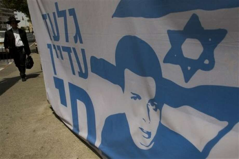 An Ultra-orthodox Jewish man walks past a banner depicting captured Israeli soldier Gilad Schalit, at a protest tent outside the Israeli Prime Minister Benjamin Netanyahu''s residence in Jerusalem, Tuesday, May 24, 2011. Netanyahu called on Hamas to release Schalit immediately, during his AIPAC address Monday. (AP Photo/Bernat Armangue)