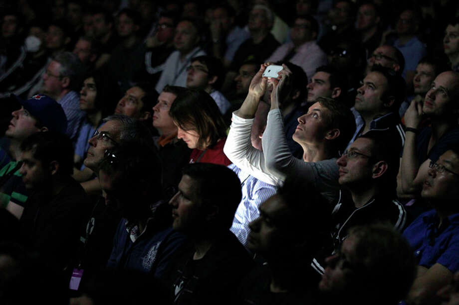 Attendees watch a video presentation on new products during the Apple Developers Conference in San Francisco, Monday, June 11, 2012. In recent years, Apple Inc. has used its Worldwide Developers Conference as an opportunity to announce new software for the iPhone, iPad and iPod Touch. (AP Photo/Marcio Jose Sanchez) / AP