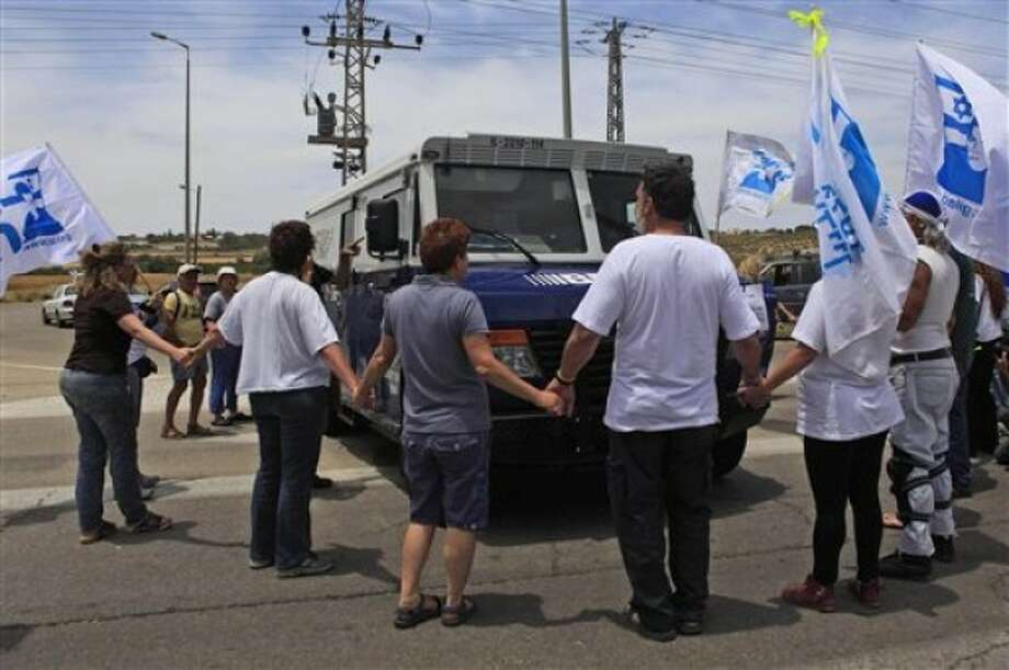 Israeli activists calling for the release of captured Israeli soldier Gilad Schalit block a Brinks armored truck on its way to transfer money to the Gaza Strip, at the Erez crossing between Israel and Gaza, southern Israel, Tuesday, May 24, 2011. Dozens of Israeli activists attempted to prevent a money transfer to the Gaza Strip Tuesday, in protest at the ongoing capture of Israeli soldier Gilad Schalit. Israeli Prime Minister Benjamin Netanyahu called on Hamas to release Schalit immediately, during his AIPAC address Monday. (AP Photo/Tsafrir Abayov)