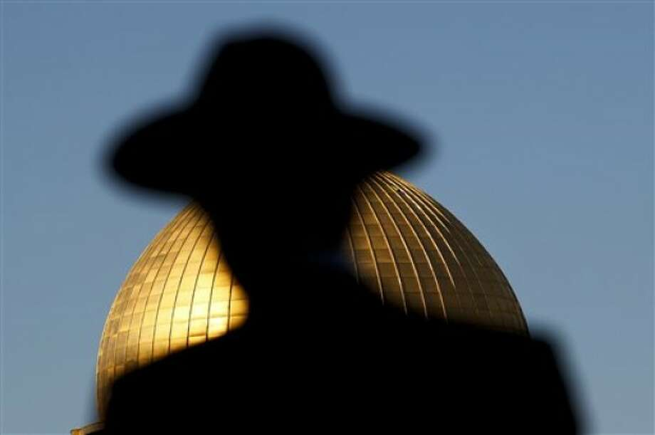 An ultra-Orthodox Jewish man is silhouetted as he stands in front of the Dome of the Rock Mosque, near the Western Wall, the holiest site where Jews can pray, in Jerusalem''s Old City, Sunday, May 22, 2011. US President Barack Obama warned America''s pro-Israel lobby on Sunday that the Jewish state will face growing isolation without a credible Middle East peace process. He defended his endorsement of a future Palestine based on Israel''s 1967 boundaries but subject to negotiated land swaps as a public expression of long-standing U.S. policy. (AP Photo/Tara Todras-Whitehill)