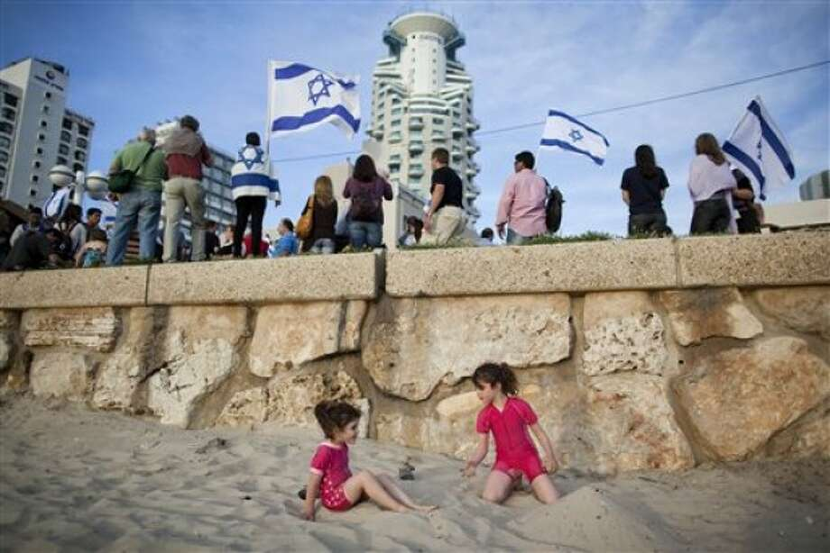 Girls play in the sand on the beach as Israeli right wing activists protest outside the US embassy in Tel Aviv, Israel, Sunday, May 22, 2011. US President Barack Obama warned America''s pro-Israel lobby on Sunday that the Jewish state will face growing isolation without a credible Middle East peace process. He defended his endorsement of a future Palestine based on Israel''s 1967 boundaries but subject to negotiated land swaps as a public expression of long-standing U.S. policy. (AP Photo/Oded Balilty)