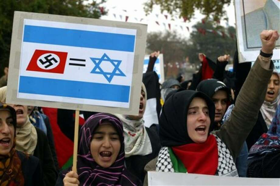 FILE - In this Nov. 10, 2006 file photo, Turkish women, holding a banner with the Nazi swastika and Star of David, chant anti-Israeli slogans during a demonstration at the Fatih mosque in Istanbul, Turkey. Israel''s ambassador to Turkey, Gabby Levy, said Sunday, May 22, 2011, that a leading Israeli theater company has been forced to cancel a play because Turkish protesters planned to disrupt the performance. (AP Photo/Osman Orsal, File)