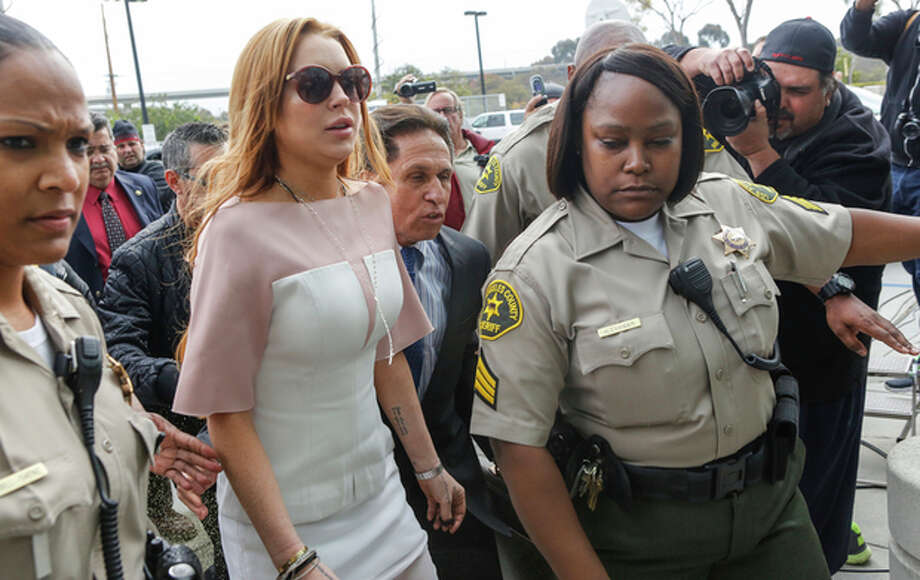 Actress Lindsay Lohan arrives at the Los Angeles Superior court Monday, March 18, 2013. Lohan is charged with three misdemeanor counts stemming from a crash on Pacific Coast Highway. She is charged with willfully resisting, obstructing or delaying an officer, providing false information to an officer and reckless driving. She is also accused of violating her probation in a misdemeanor jewelry theft case. (AP Photo/Damian Dovarganes) / AP