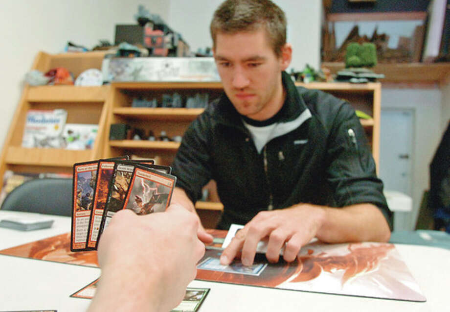 Hour photo / Erik TrautmannJames Donovan plays Magic with Alan Breitman at the new gaming store, Battleground Gaming on Main Avenue. / (C)2012, The Hour Newspapers, all rights reserved