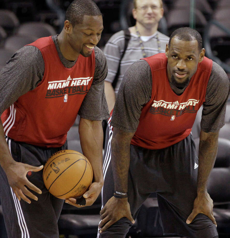 Miami Heat guard Dwyane Wade, left, and forward LeBron James talk during practice, Monday, June 11, 2012, in Oklahoma City. Game 1 of  NBA basketball finals between the Heat and Oklahoma City Thunder is scheduled for Tuesday. (AP Photo/Sue Ogrocki) / AP