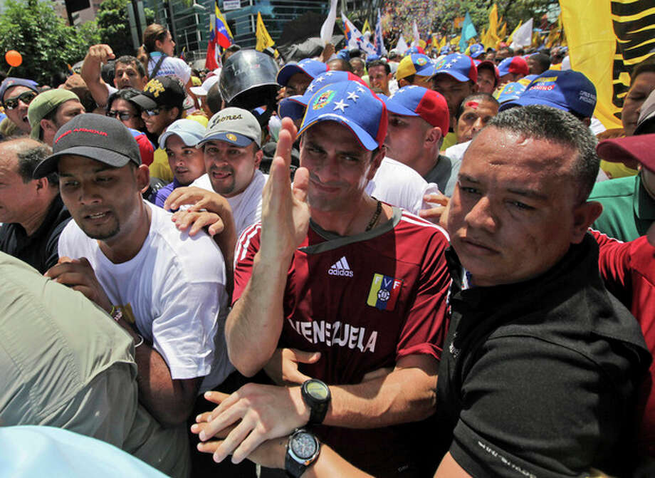 Surrounded by supporters, opposition presidential candidate Henrique Capriles, center, gestures during a march before registering his candidacy for the presidency in Caracas, Venezuela, Sunday, June 10, 2012. (AP Photo/Fernando Llano) / AP