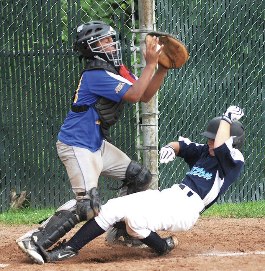 Hour Photo/John Nash Wilton's Collin Kahal, right, slides safely under the tag of the Seymour catcher during Sunday's Section 1 tournament game played in Bridgeport.