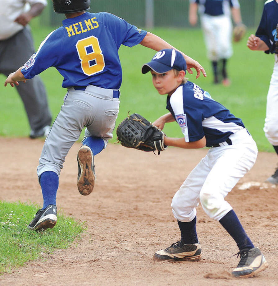 Hour Photo/John Nash Wilton second baseman Jack Gioffre looks to throw to first after fielding a ground ball as a Seymour runner races by him.