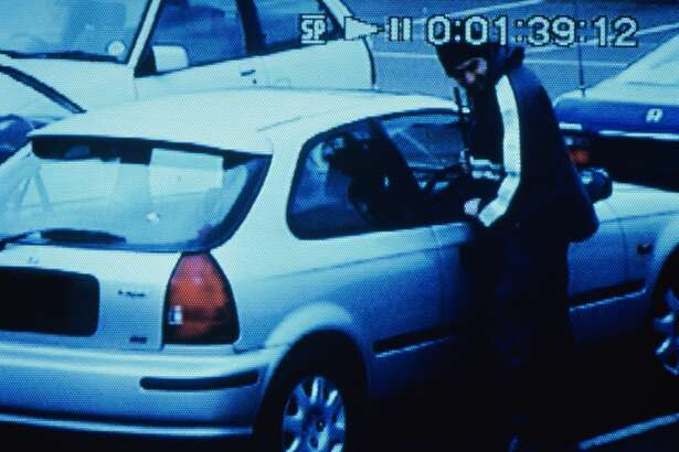 Man trying to break into car outdoors (video still)
