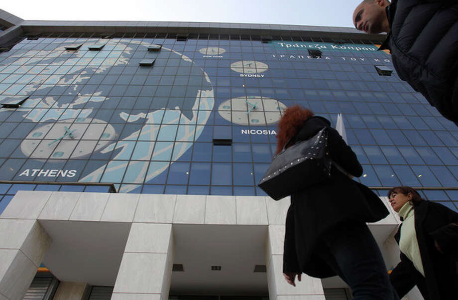Pedestrians pass outside the headquarters of Bank of Cyprus as the bank will remain closed for two days in Athens, Tuesday, March 19, 2013. Banks stocks were sharply lower on the Athens Stock Exchange, as trading resumed for the first time in Greece since the details of a bailout in Cyprus and a shock levy on bank deposits were announced. Following a public holiday Monday, Greek branches of the Cypriot lenders the Bank of Cyprus, Laiki Bank and Hellenic will remain closed Tuesday and Wednesday. (AP Photo/Thanassis Stavrakis) / AP